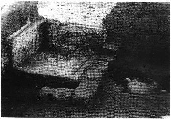 A stone bath with plastered sides and drain. Just below the outlet of the bath, water drained into a vase perforated at the bottom and cemented into the earth.