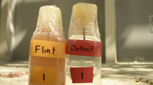 Water samples from the Flint River and Detroit's Lake Huron supply. Image courtesy of the ACLU of Michigan - http://aclumich.org/sites/default/files/images/Flint%20water.png